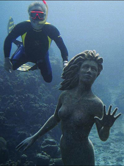 Photo of Simon Morris swiming with bronze statue Amphitrite in Grand Cayman